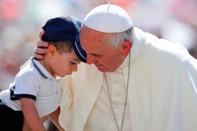Le pape François embrasse un jeune garçon, au cours de l'audience générale, le 19 juin 2013 sur la place Saint-Pierre. / Stefano Rellandini/Reuters